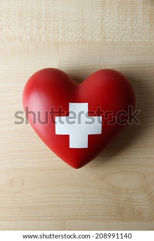Red heart with cross sign on wooden background