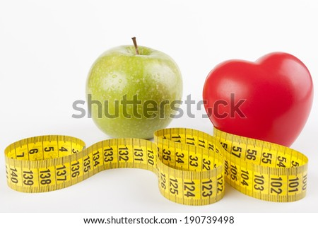 Red heart with green wet apple and yellow measuring tape isolated on white background