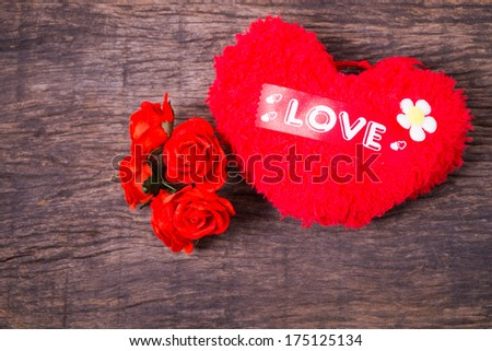 Red heart with love word  decorate with roses on wooden table top