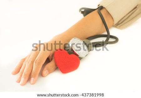 Red heart with woman arm checking blood pressure. - stock photo
