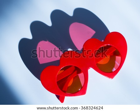 Red hearted sunglasses with pink shadow - stock photo