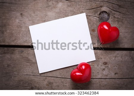 Red hearts and empty tag for text on aged wooden background. Selective focus. - stock photo
