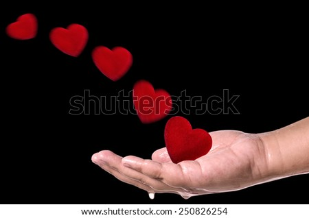 Red hearts fly into hand on black  background . Love concept - stock photo