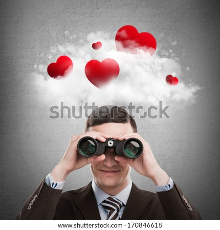 Red hearts flying in cloud overhead of man looking through binoculars. Valentine's day background - stock photo