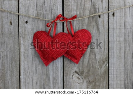 Red hearts hanging on clothesline with wood background - stock photo
