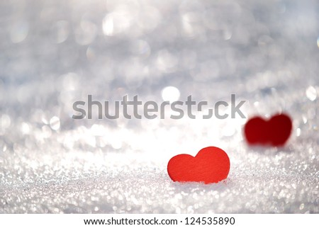 Red hearts in glittering snow with shallow depth of field - stock photo
