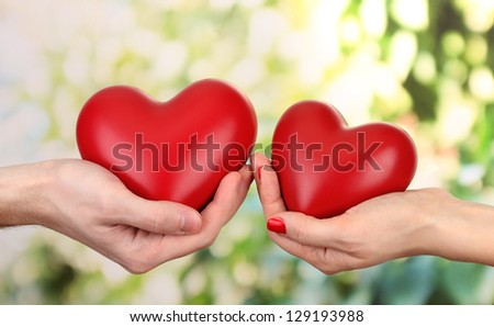 Red hearts in woman and man hands, on green background