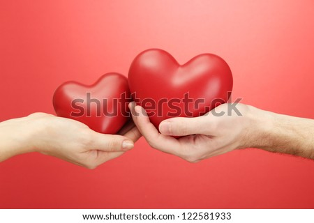 Red hearts in woman and man hands, on red background