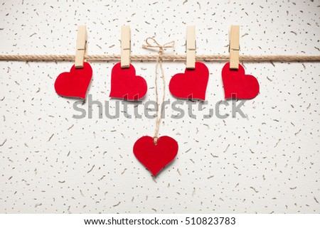 red hearts on a clothespin on a white wall