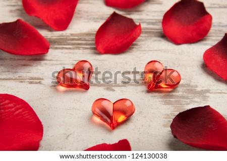 red hearts on the wooden board with petals