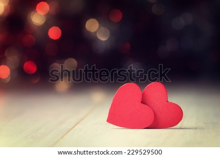 Red hearts on wooden table against defocused lights. - stock photo