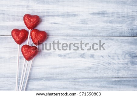 Red hearts over light blue wooden background
