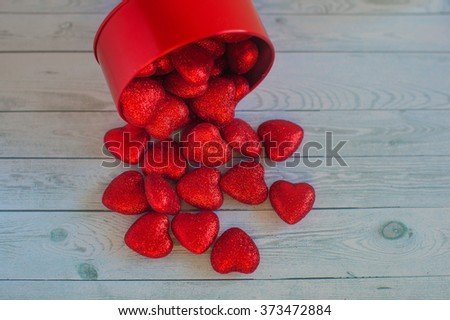 Red hearts spill out of the red box on the table
