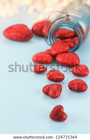 Red hearts spilling from a blue mason jar filled with hearts. Extreme shallow depth of field with selective focus on little heart in the foreground. - stock photo