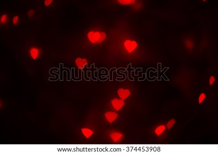Red hearts texture. Hearts Bokeh in dark. Defocused lights background. Color Bokeh on a dark background with hearts for use in graphic design. Valentine's style lights. St. Valentine's Day. - stock photo