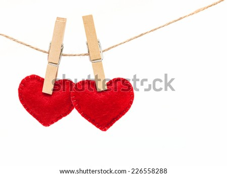 Red hearts with clothespins hanging on clothesline isolated on white background. Valentines Day - stock photo