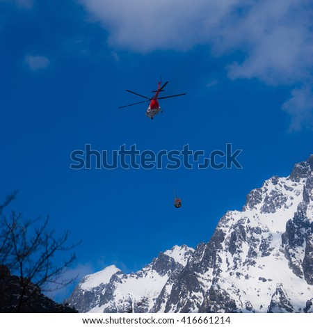 Red helicopter at the winter mountains