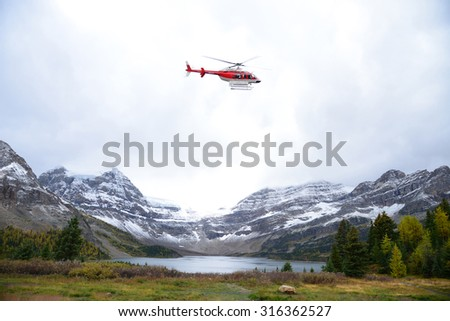 red helicopter taking off near snow mountain in alberta, canada
