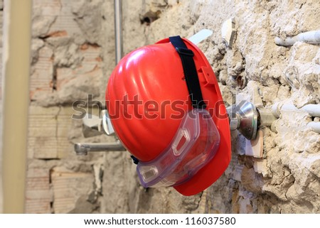 Red helmet and goggles on work place