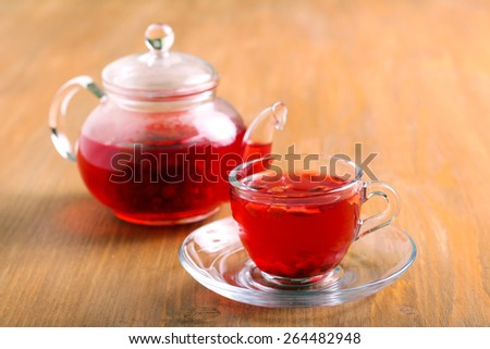 Red herbal and fruit tea in cup and tea pot - stock photo