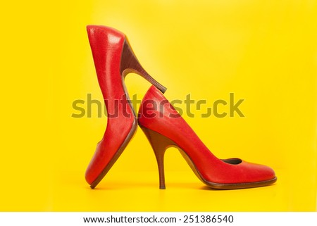 red high heels shoes on yellow background - stock photo