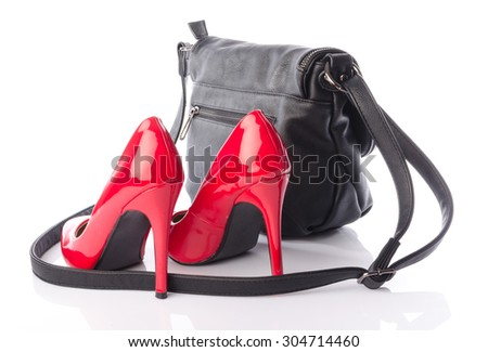 Red high heels shoes with a black handbag, isolated on white