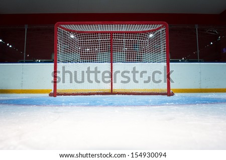 Red hockey goal. Front view from ice - stock photo