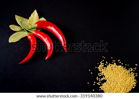 Red hot chili pepper, mustard and laurel with copy space on black background. Vegetable healthy fresh food. Color heat spice, ingredient. - stock photo