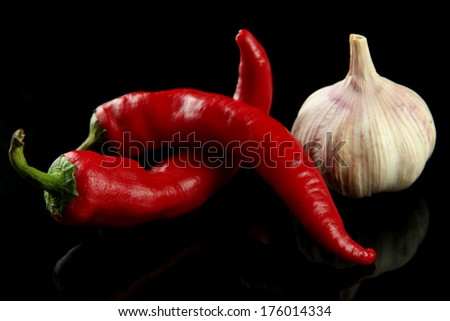 Red hot chili peppers and garlic, isolated on   black - stock photo