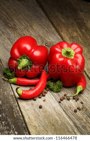 Red Hot Chili Peppers and red sweet paper over wooden background - stock photo