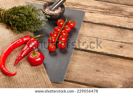 Red Hot Chili Peppers and ripe cherry tomatoes on a chopping board