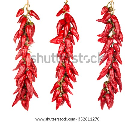 Red hot chili peppers hanging on a three ropes isolated on the white background  - stock photo