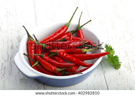 Red hot chili peppers heap on the wood background - stock photo