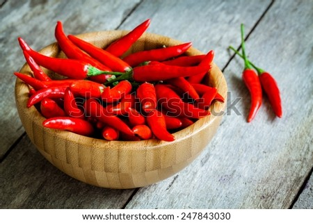 red hot chili peppers in a bowl on wooden rustic background - stock photo