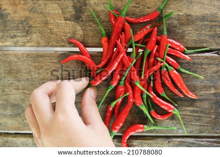 Red hot chili peppers on old wooden table background - stock photo
