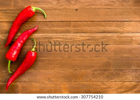 Red hot chili peppers on old wooden table, copy space - stock photo
