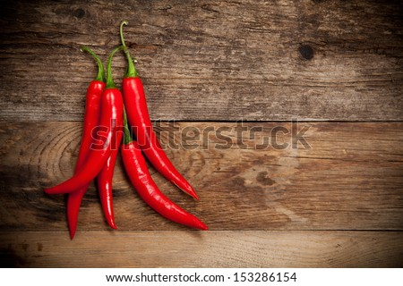 Red hot chili peppers on old wooden table with place for text - stock photo