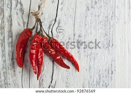 Red hot chili peppers on white wooden table - stock photo