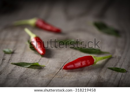 Red hot chili peppers on wood background with leaves - stock photo