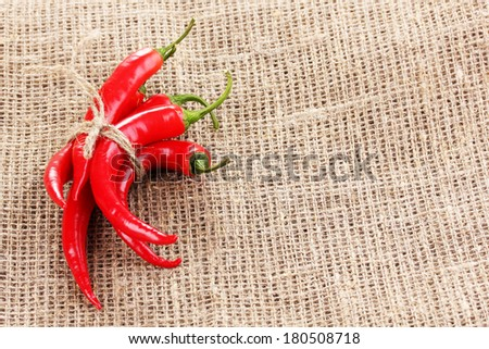 Red hot chili peppers tied with rope on sackcloth
