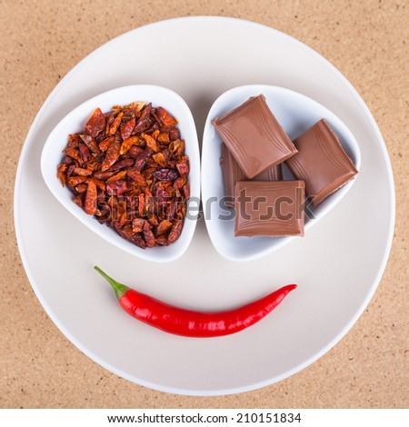Red hot chili peppers with chocolate on plate, over light wooden background. - stock photo