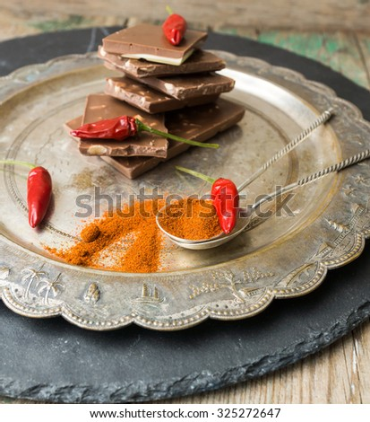Red hot chili peppers with chocolate on vintage plate, over light wooden background.