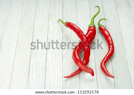 red hot chilies on white wooden table background