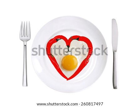 red hot chilly peppers and fried egg on white plate isolated on white background