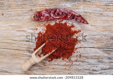 Red hot dry chili pepper and paprika on wood background - stock photo