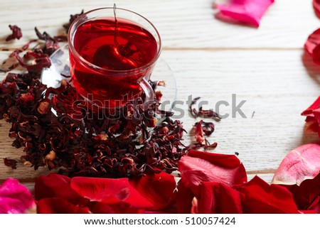 Red Hot Hibiscus tea in a glass mug on a wooden table among rose petals and dry tea custard with metallic heart