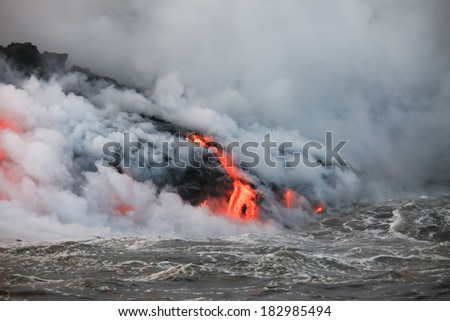 Red hot lava flowing into Pacific Ocean on Big Island, Hawaii  - stock photo
