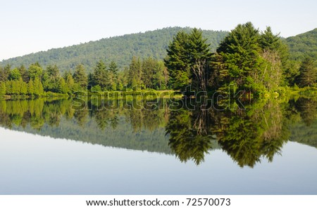 Red House Lake, green forest and mountains - stock photo