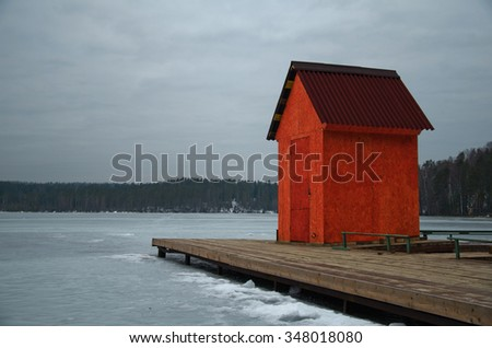 red house on pier, winter landscape of the shoreline of the lake with a dock - stock photo