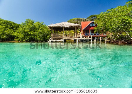 Red house on stilts with gazebo at secluded beach in Caribbean